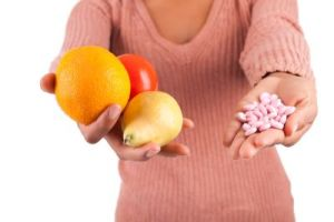 A woman holding fruits and diarrhea pills.
