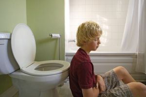 A young boy leaning back on the toilet looking sick.