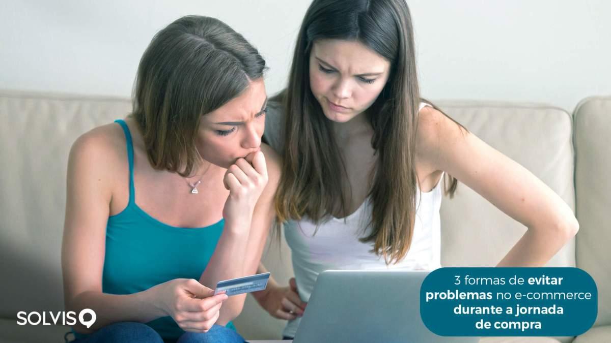 Duas mulheres brancas sentadas em um sofá olhando para um notebook segurando um cartão na mão.