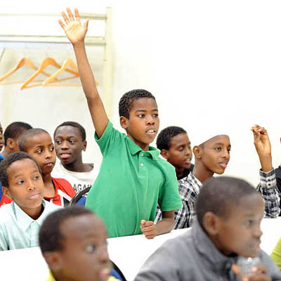 A Somali boy raising his hand in a classroom