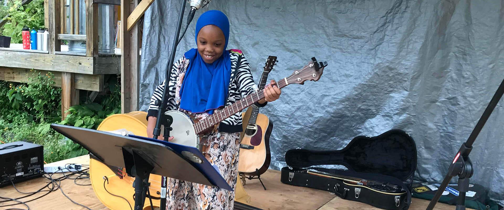 A Somali Bantu girl playing banjo on stage