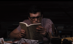 Ethan reading the same book as Lena the night after their conversation.