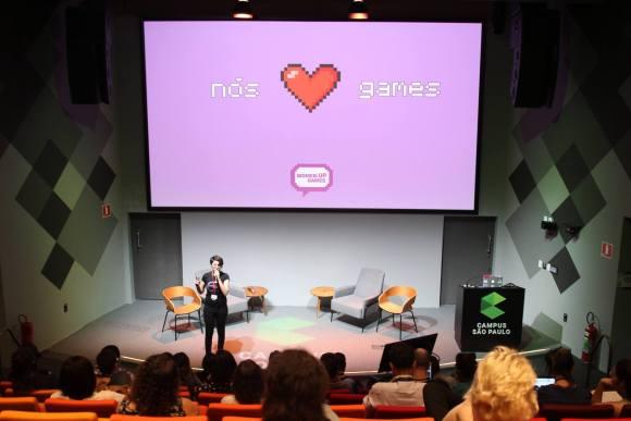 Ariana palestrando com a tela Nós coração games