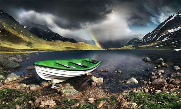 Barco em lago com arco-íris ao fundo