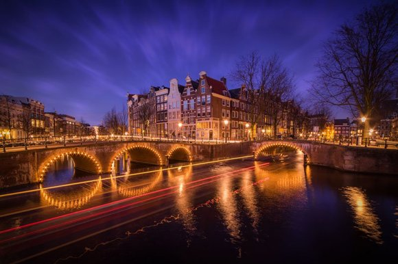 Ponte de Amsterdam com desenho de luz dos barcos em alta exposição