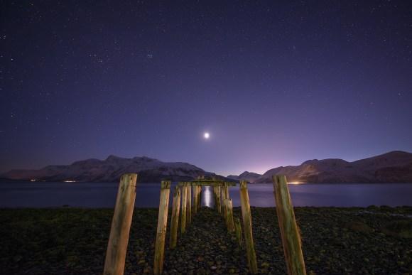 Estrelas e lua sobre um pier em Fjord, Noruega