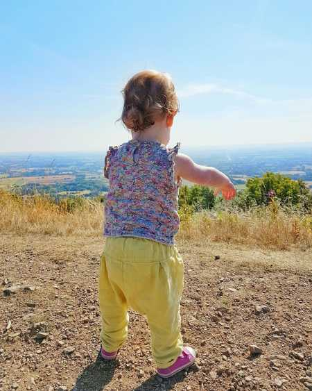 Girl looks out at view from hill by Someone's Mum