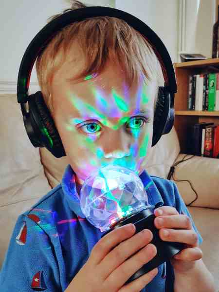 Boy with Bluetooth headphones and sensory toys which make good gifts for autistic children. Photo by Someone's Mum.