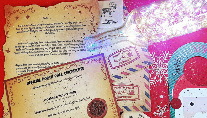 The gorgeous personalised letter and extras from Magic Santa Letters next to a fairy light lamp. Photo by Someone's Mum