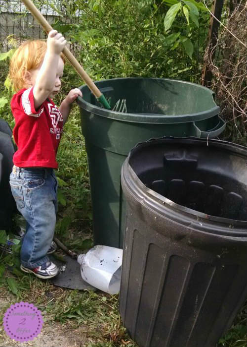 toddler with compost trash cans