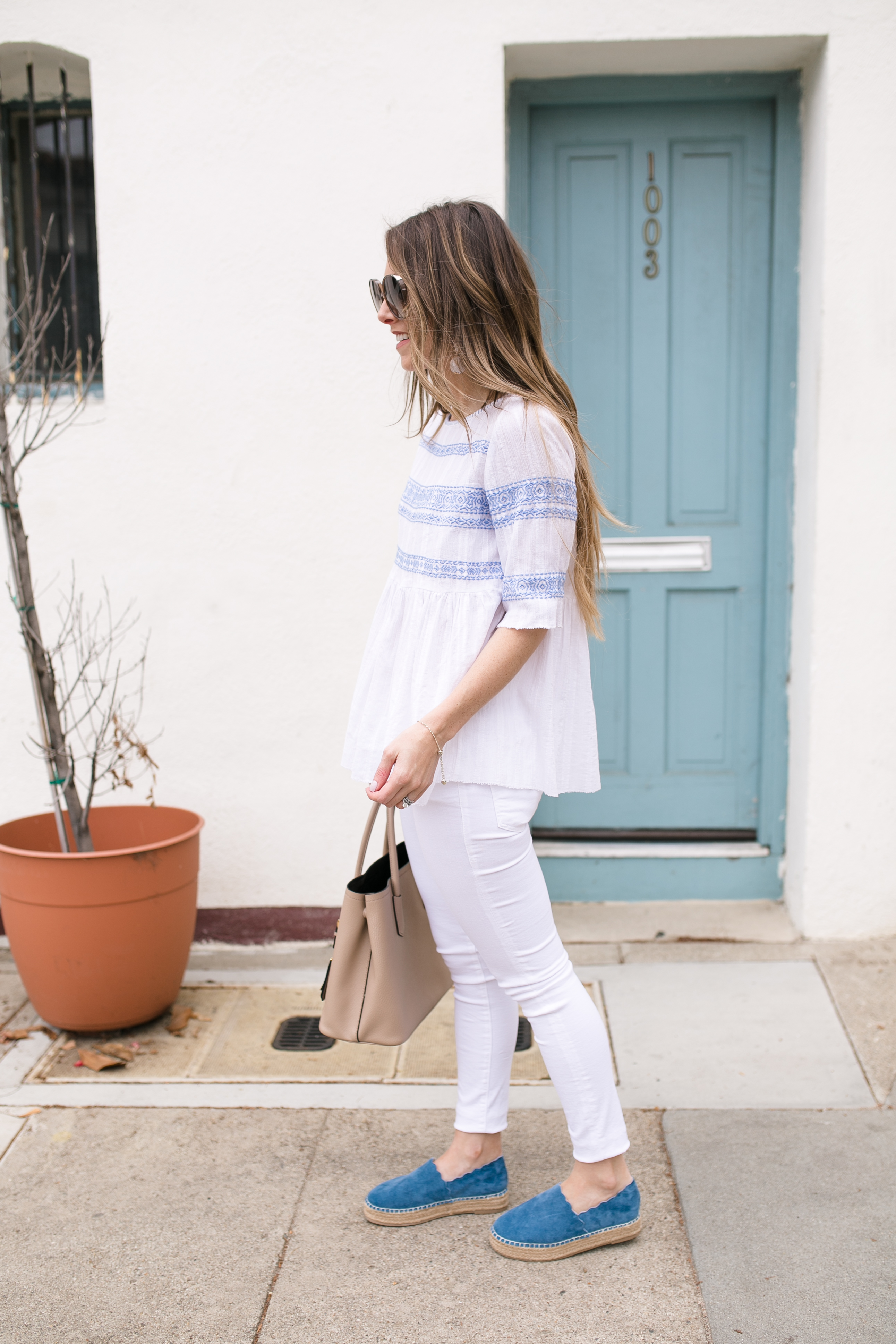 Style blogger Daryl-Ann Denner wearing Chloe Espadrilles dupes and an embroidered blue and white top with white jeans