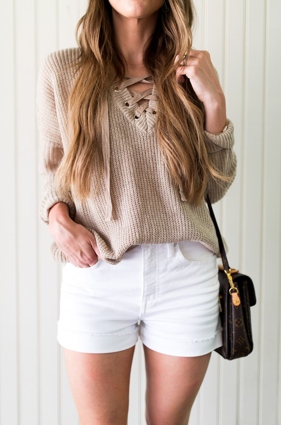 Daryl-Ann Denner wearing white shorts and lace-up sweater