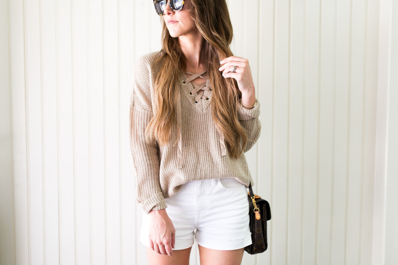 Daryl-Ann Denner wearing white shorts and lace-up summer sweater