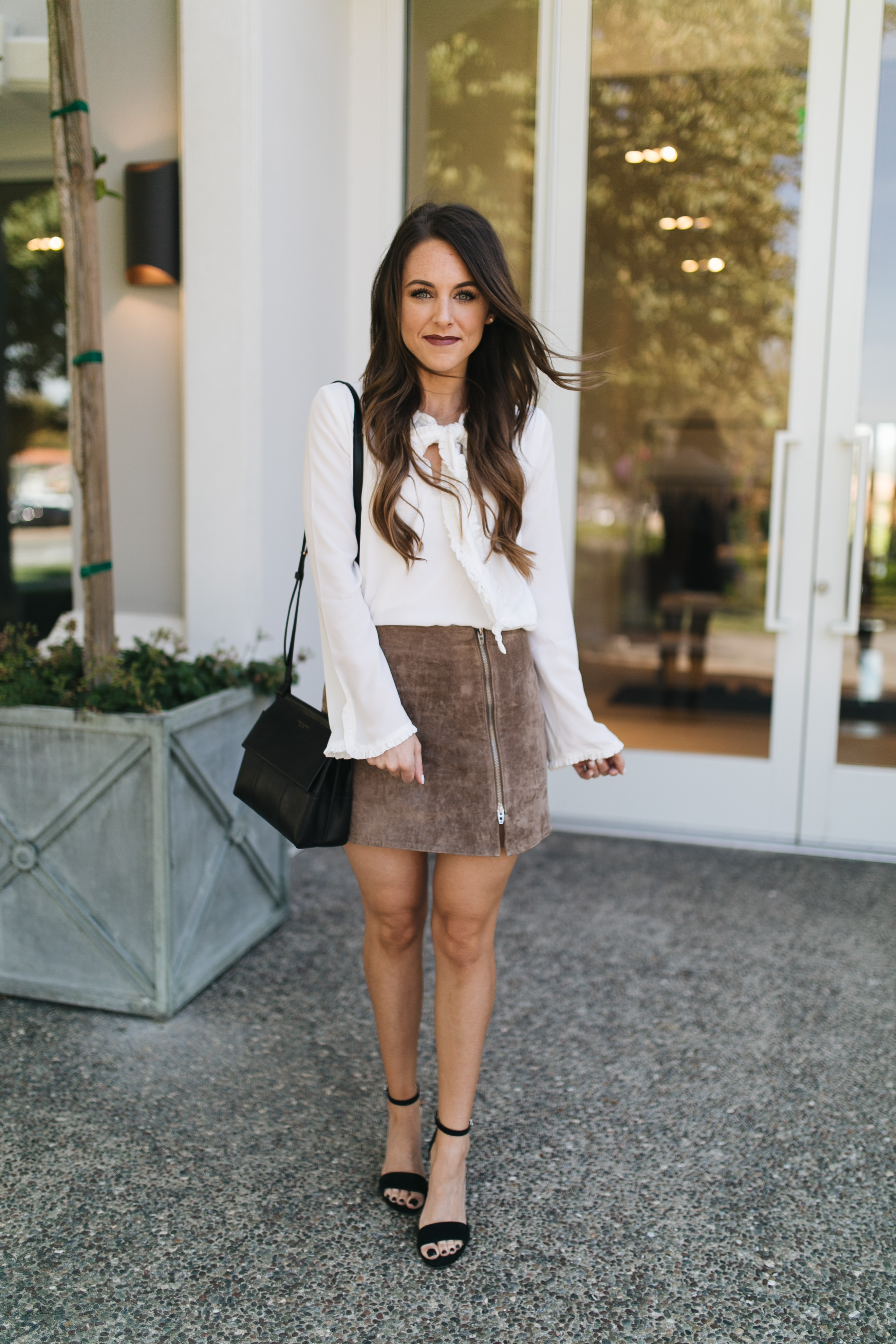 Style blogger Daryl-Ann Denner shares inspiration for a weekend date night outfit for Fall and styles a suede miniskirt with a white bow blouse and heels