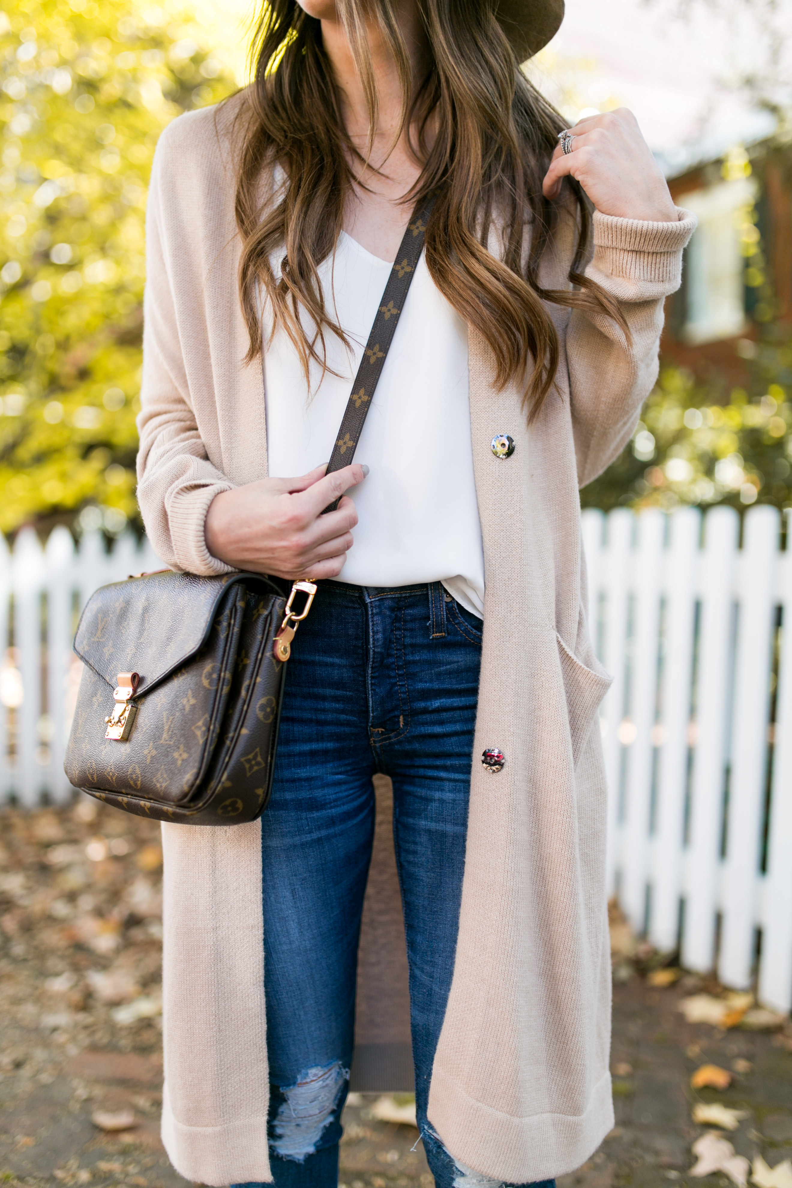 Style blogger Daryl-Ann Denner wears neutral cardigan and beige wide brim hat and louis vuitton crossbody bag creating the perfect fall outfit in georgetown
