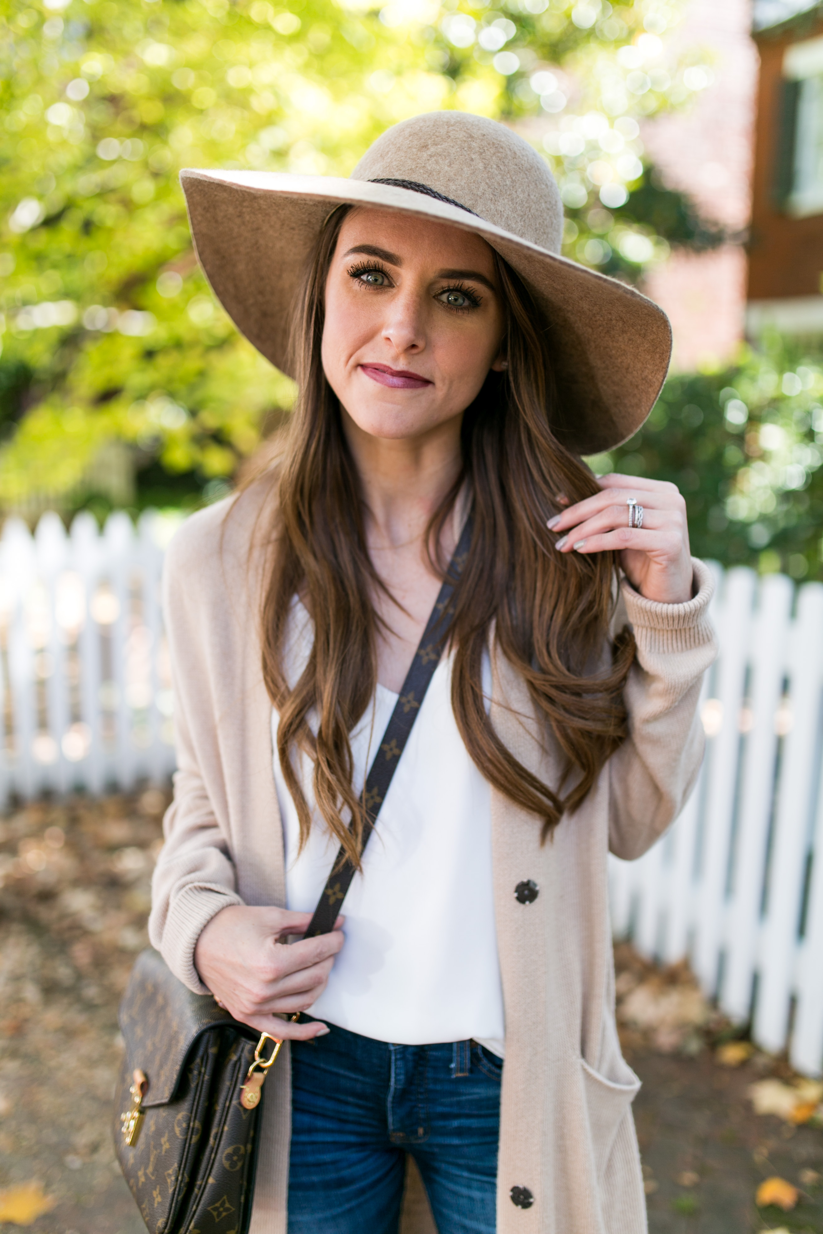 Style blogger Daryl-Ann Denner wears neutral cardigan and beige wide brim hat creating the perfect fall outfit in georgetown