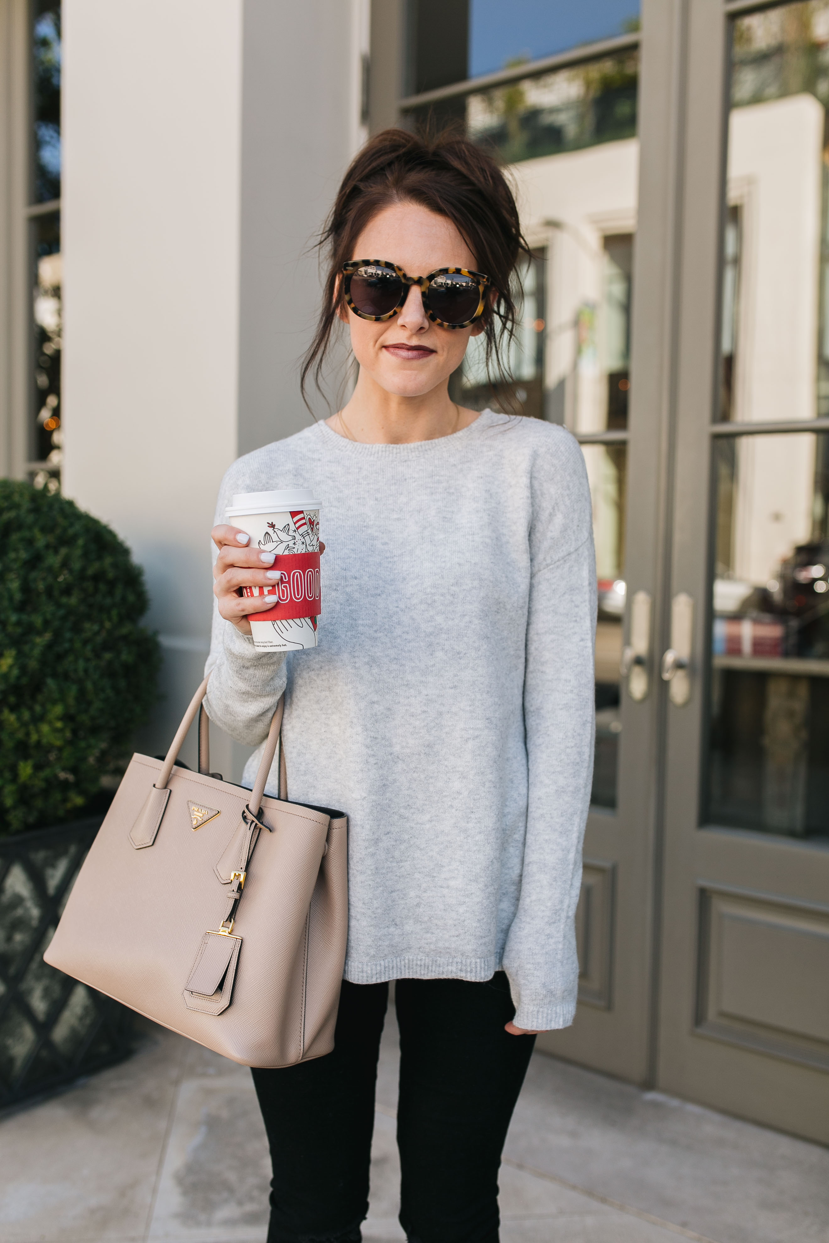 Style blogger Daryl-Ann Denner wears a bow back sweater from Nordstrom, black ripped skinny jeans from Abercrombie & Fitch, a nude Prada bag, leopard print sunglasses and a hot chocolate in a Starbucks holiday cup.
