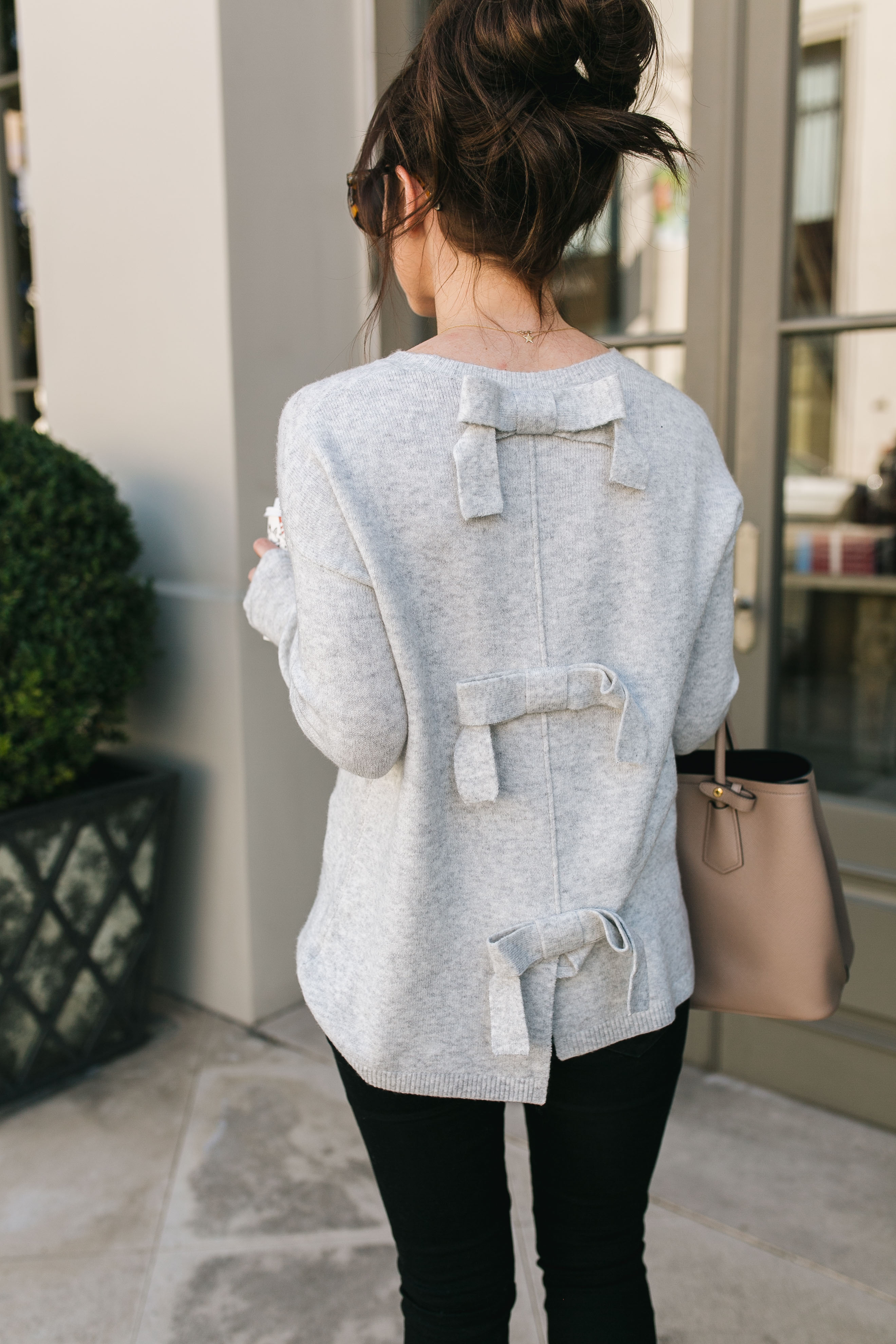 Style blogger Daryl-Ann Denner wears a bow back sweater from Nordstrom, black ripped skinny jeans from Abercrombie & Fitch, a nude Prada bag, black leather booties and a hot chocolate in a Starbucks holiday cup.