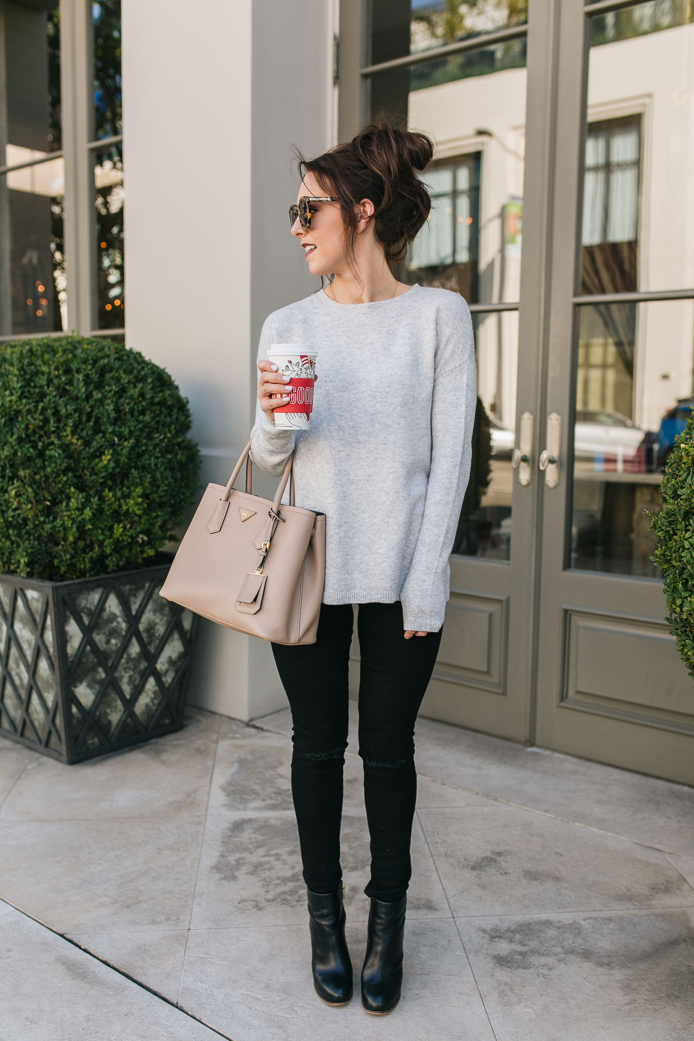 Style blogger Daryl-Ann Denner wears a bow back sweater from Nordstrom, black ripped skinny jeans from Abercrombie & Fitch, a nude Prada bag, black leather booties, leopard print sunglasses and a hot chocolate in a Starbucks holiday cup.