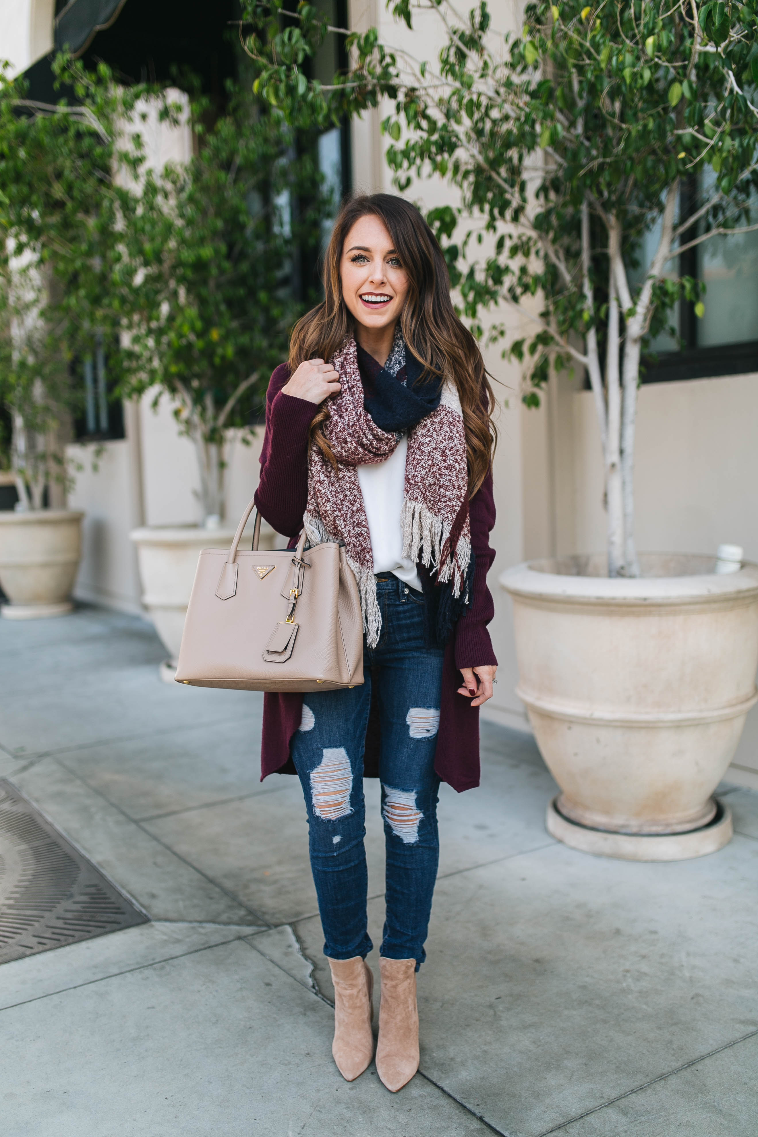 Style blogger Daryl-Ann Denner shares the best cardigan under $100 with cozy scarf, ripped Good American jeans, and Prada Double bag