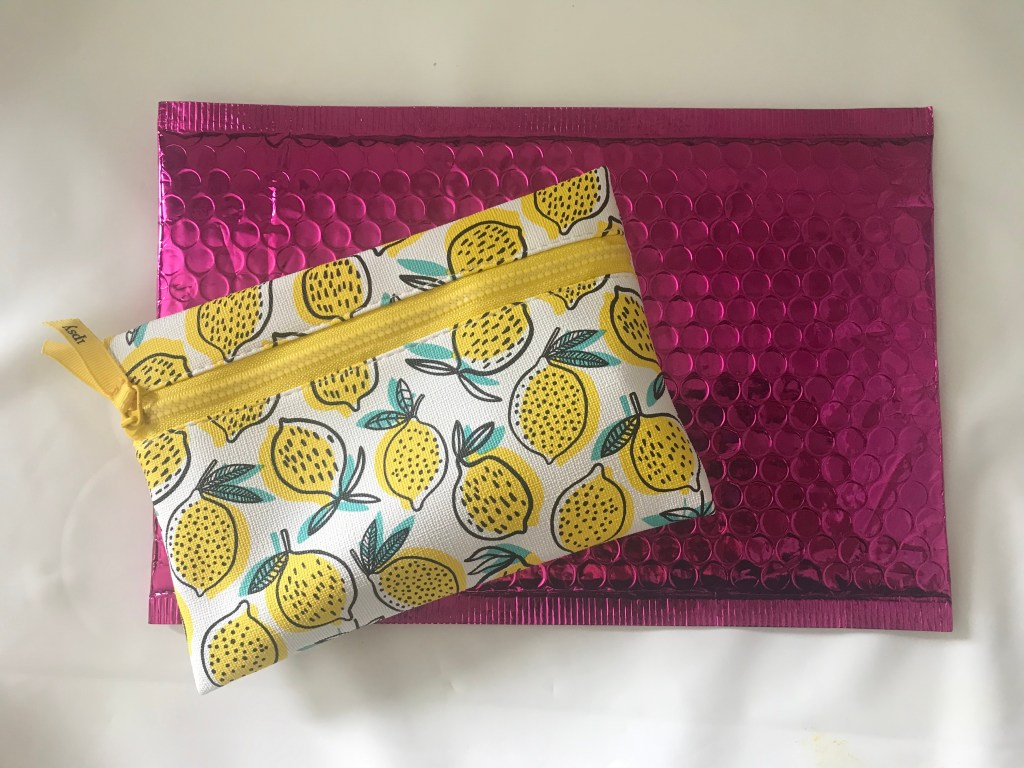 makeup bag with lemons on it. Pink shiny package it arrived in.