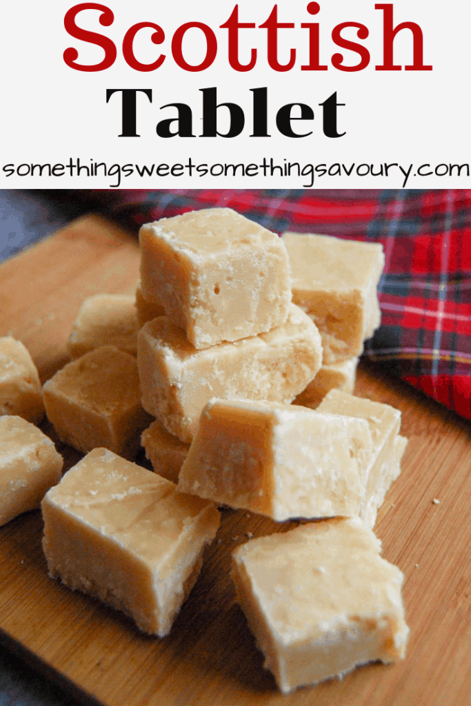 Pieces of Scottish Tablet on a wooden board with a tartan tablecloth in the background.