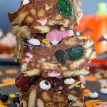 3 pieces of rocky road piled on top of each other, with green cherries, biscuit pieces and edible candy eyes with an orange pumpkin in the background