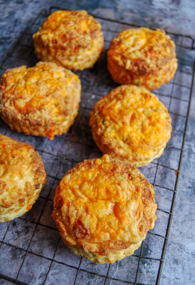6 Cheese scones on a black cooling rack on a dark grey background.