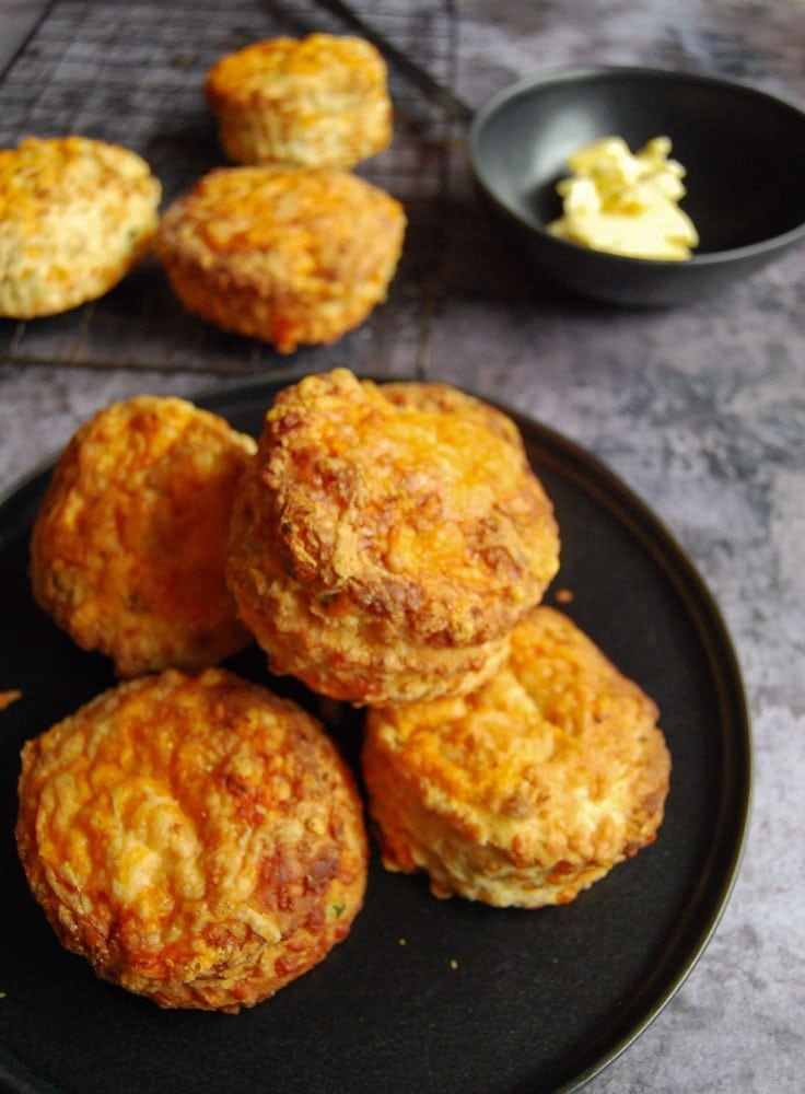 A pile of cheese scones on a black plate. A black bowl of butter and more scones on a wire cooling rack sits in the background.