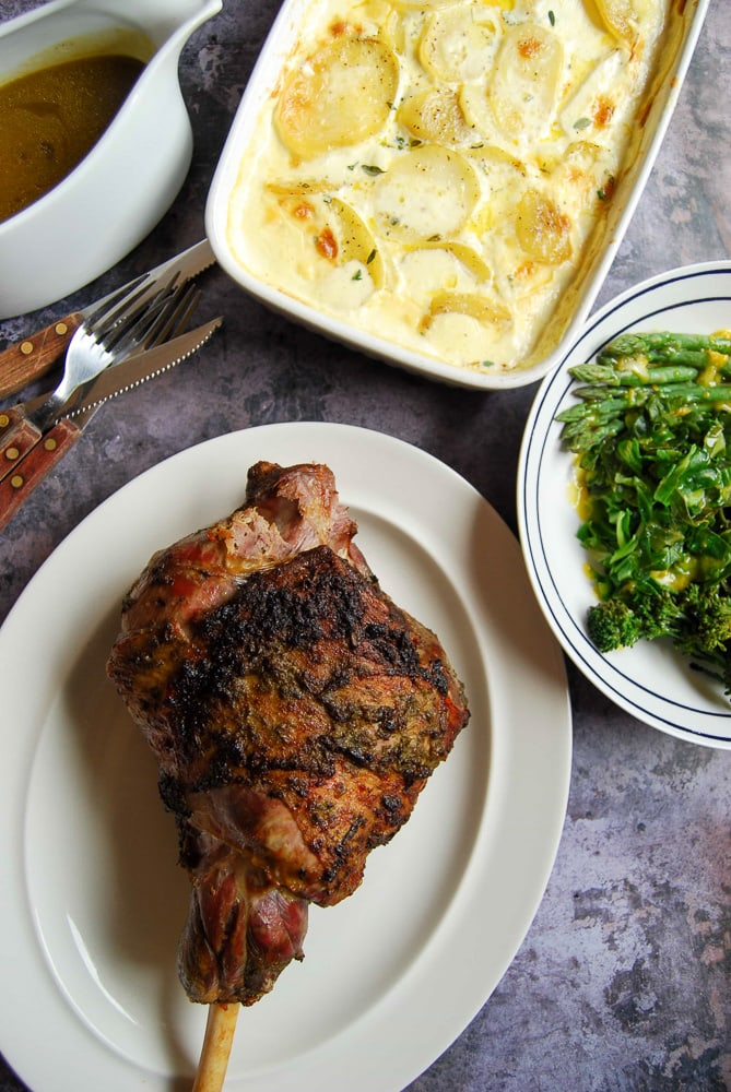 A leg of roast lamb with wild garlic and rosemary on a white plate with potato grain, Spring greens and a jug of gravy on the side.