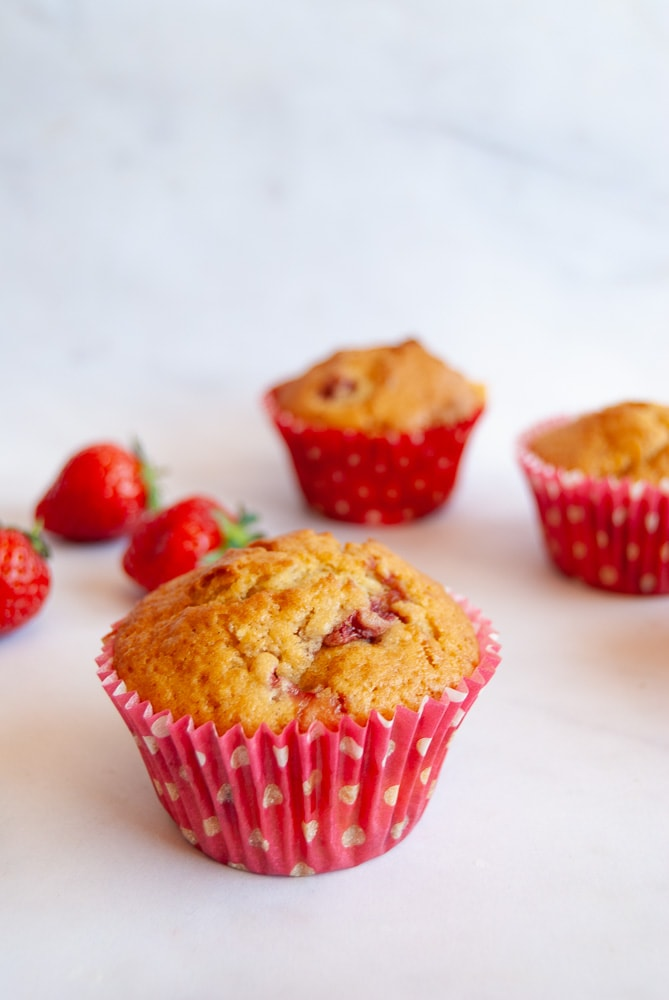 A strawberry and white chocolate muffin on a white marbled background. More muffins and fresh strawberries can be seen in the background