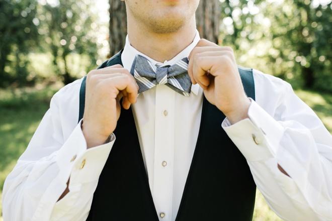 Groom fixing his bow tie.