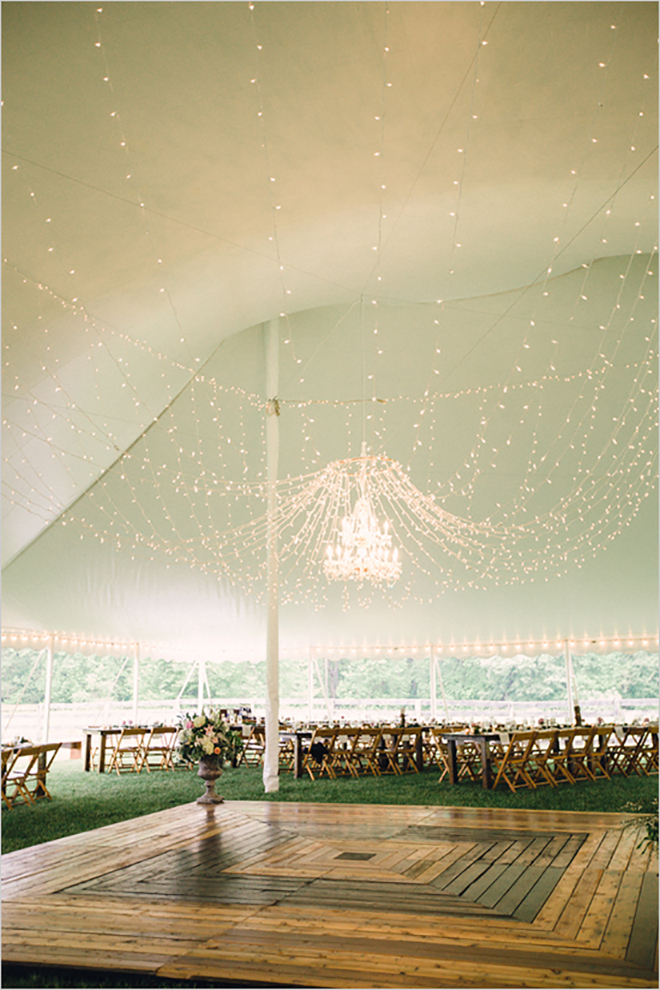 twinkle lights and a wired chandelier sets the mood in a wedding tent