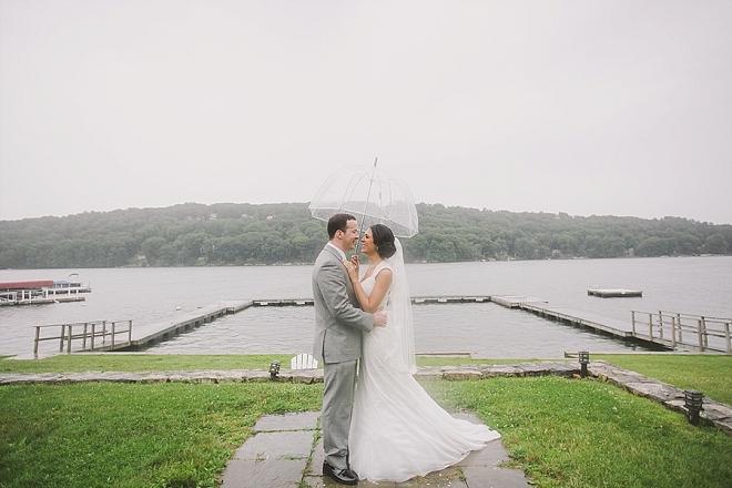 How stunning is this rainy lakeside umbrella photo?! We LOVE rainy weddings!