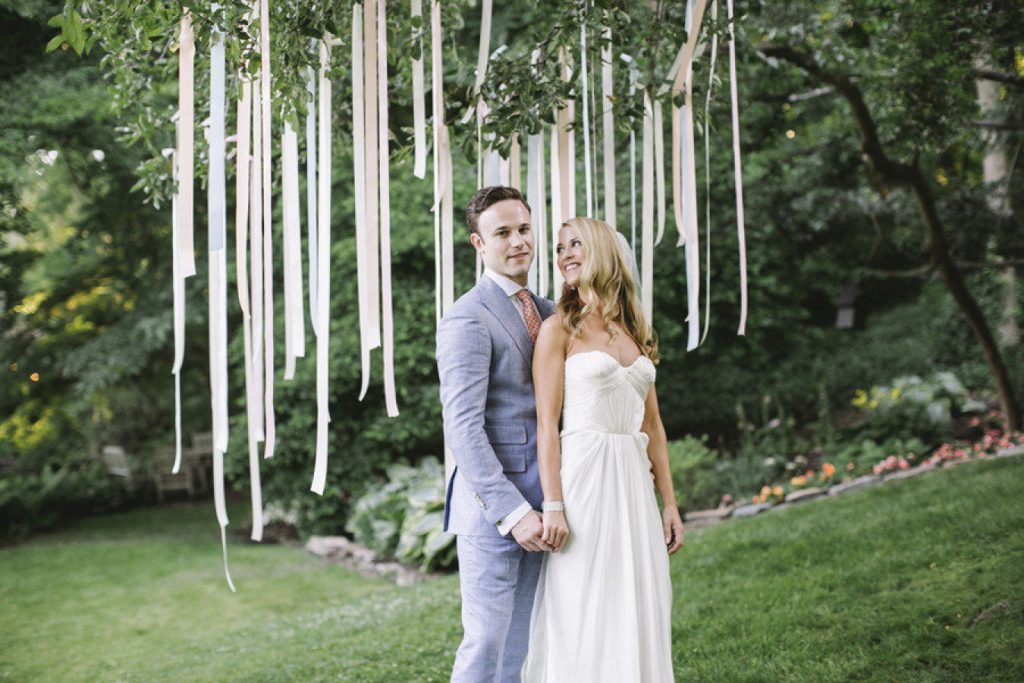 Easy Wedding DIY: Ribbons hanging from a tree as a photo backdrop.