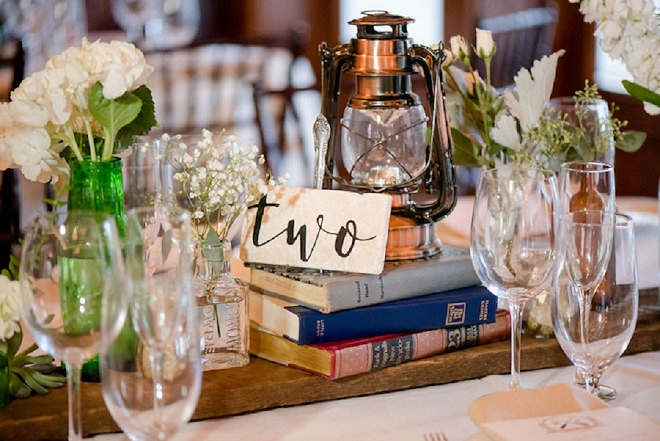 We love these book and greenery centerpieces at these teacher's lakeside wedding!