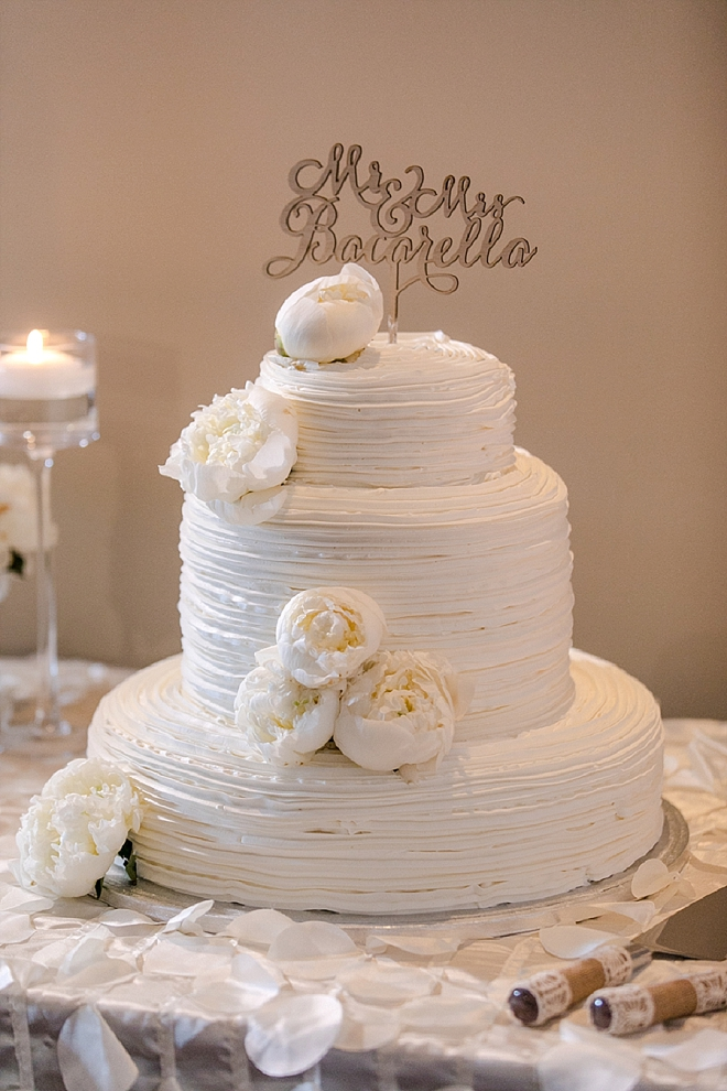 Gorgeous all white wedding cake with gold cake topper!