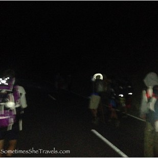 people walking on a road in the dark