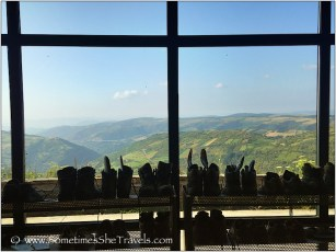 Boots on rack in front of a window with view of green mountains