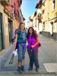 Two women wearing backpacks and holding hiking poles