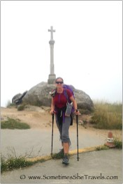 Woman with backpack and hiking poles in front of a cross on a rock