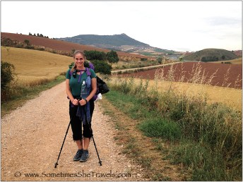 Woman with backpack and hiking poles on trail in field