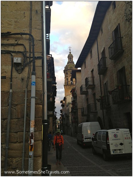 A pilgrim takes an early morning walk down the main street of Puente la Reina