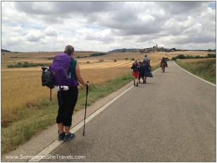 woman with backpack watching other backpackers heading toward hill town