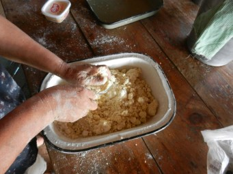 Mixing mbeju dough by hand. It requires a lot of squeezing to distribute the moisture throughout the fairly dry dough.