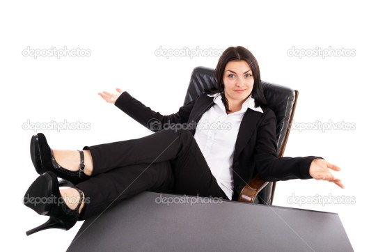 Young businesswoman sitting in an armchair with legs on table