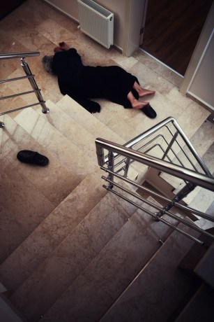 Senior woman lying on floor after falling down the stairs