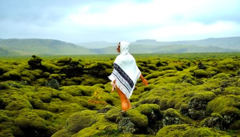 woman wearing a poncho in Iceland green hills