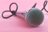 20324878-metal-microphone-with-cord-lying-on-pink-background