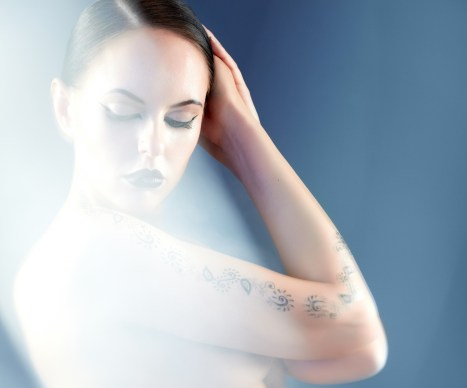 Portrait of naked woman with tattoo surrounded by mist